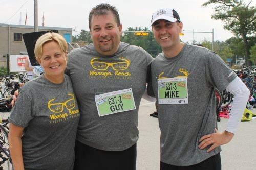 a female and two males stand side by side in grey shirts that read Wasaga Beach Triathalon