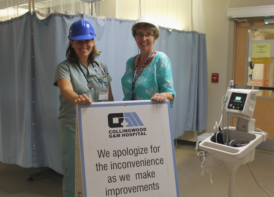 Two females wearing hard hats, stand in front of a blue curtain and behind a sign that reads we apologize for any inconvenience as we make improvements